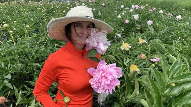 Une femme dans un champ de pivoines