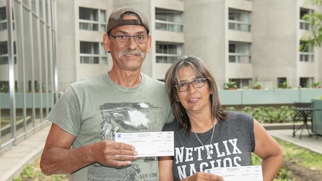 Manon et Georges avec deux chèques devant la caméra.