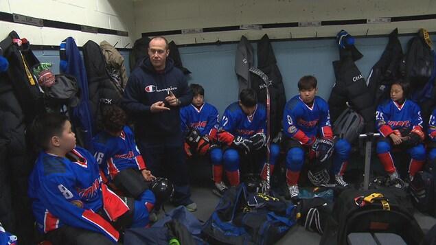 Un entraîneur parle aux hockeyeurs dans la chambre des joueurs.
