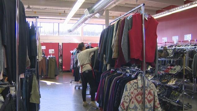 Des rayons de vêtements et de chaussures avec une personne au centre qui cherche dans un rayon.