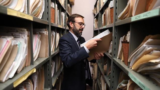 L'avocat Manuel Johnson consulte un dossier aux archives de son bureau des Services communautaires juridiques de Pointe-Saint-Charles et Petite-Bourgogne