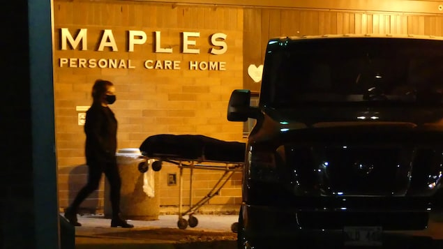 Le bâtiment du foyer de soins de longue durée avec l'enseigne de Maples. Il est possible de voir une dame avec un masque, une camionnette et une civière.