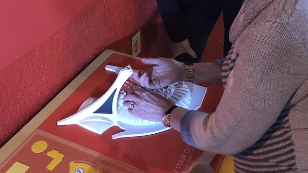 Une personne aveugle touche la maquette tactile du Stade olympique de Montréal pour mieux saisir les particularités architecturales.