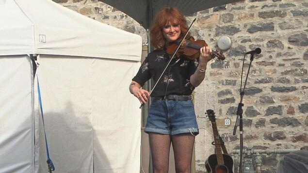 Une femme joue du violon sur une scène