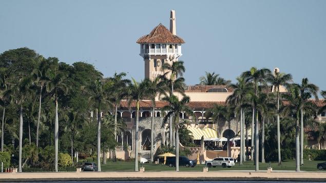 Les bâtiments principaux du club Mar-a-Lago, entourés de palmiers.