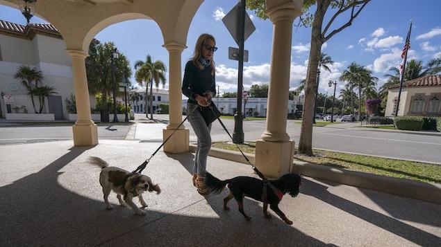 Une femme tient deux chiens en laisse et passe sous une arche.