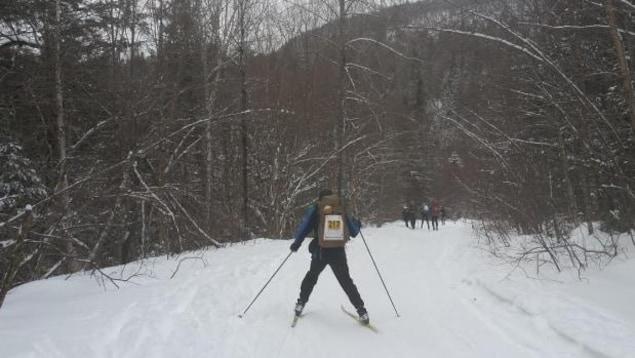Un participant du Marathon canadien de ski dans la forêt.
