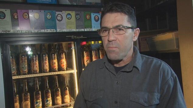L'homme est interviewé devant un étalage de produits de la microbrasserie BDT