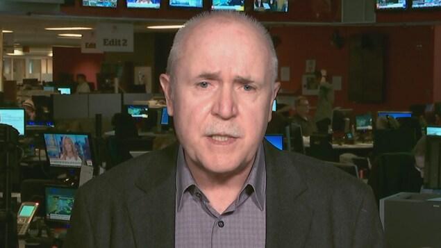 Dans une salle des nouvelles, un homme aux cheveux courts gris et avec une moustache, parle l'air sérieux.