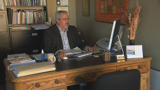 Un homme assis à son bureau travaille à l'ordinateur.