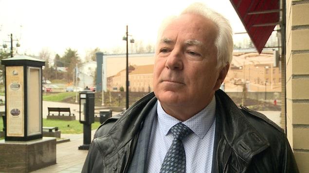 Un homme en complet cravate vêtu d'un manteau de cuir à l'extérieur lors d'une journée grise.