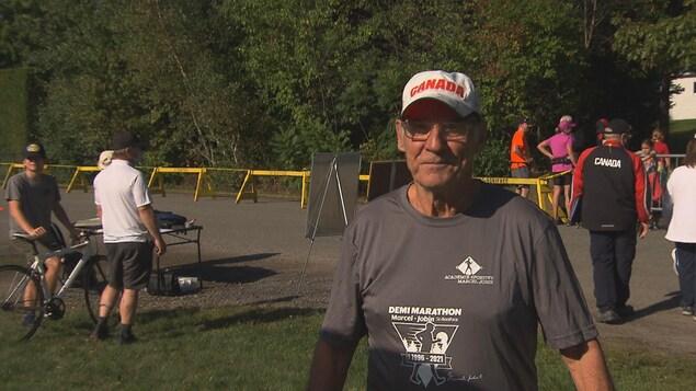 Marcel Jobin prend la pose en bordure du parcours du Demi-marathon où se trouvent quelques participants et des organisateurs.