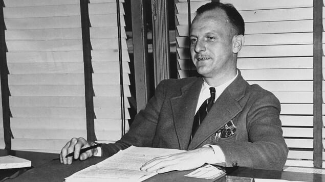 Le directeur de la radio de la Société Radio-Canada, Marcel Ouimet, assis à son bureau, en 1947.
