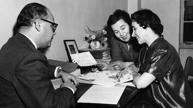Dans un bureau, Claude Mailhiot, Marcelle Barthe et Magdeleine Mailhiot, sont assis à une table et dépouillent le courrier, en discutant.
