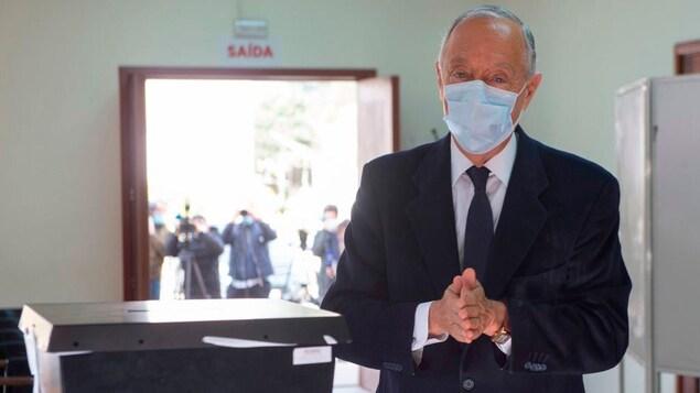 Marcelo Rebelo de Sousa porte un masque chirurgical et joint les deux mains devant lui. À côté de lui se trouve une boîte de vote dans un bureau de scrutin.