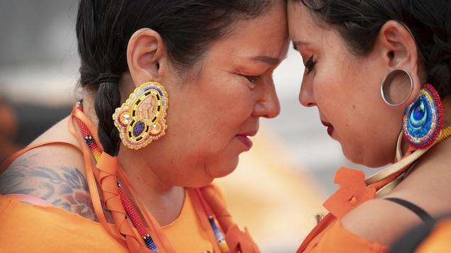 Deux femmes autochtones se serrent, les larmes aux yeux.
