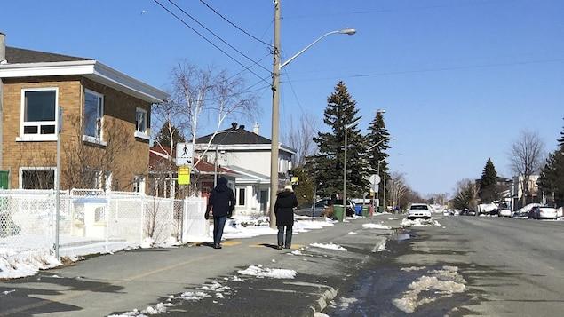Deux personnes marchent sur le trottoir.