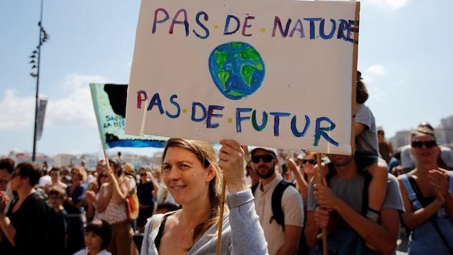 Une femme tient une pancarte sur laquelle on peut lire «Pas de nature, pas de futur».
