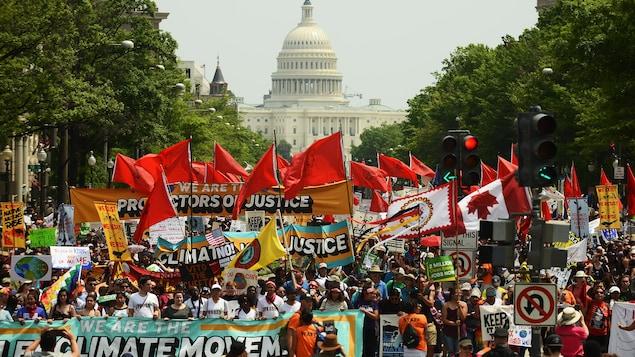 Des manifestants avec des banderoles et des drapeaux colorés marchent sur l'avenue Pensylvannie avec le Capitole au fond.