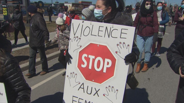Une femme tient un pancarte qui dénonce la violence faite envers le femmes.