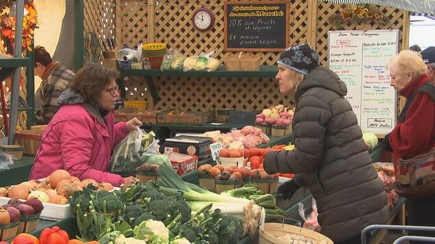 Une femme achète des légumes.