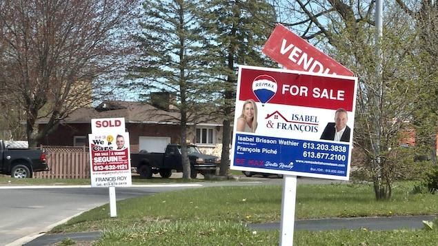 Deux pancartes d'agences immobilières indiquant «vendu» sur des terrains voisins dans un quartier résidentiel.