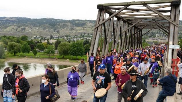 Des centaines de personnes traversent un pont à pied.