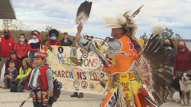 Un homme et un garçon, en habits traditionnels autochtones, dansent et des personnes rassemblées assistent à la prestation.