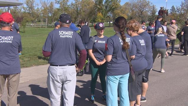 Des participants de la marche vêtus de chandails assortis se tiennent debout en cercle et discutent.