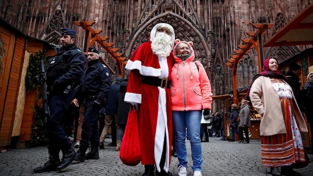 Une femme pose avec le père Noël en présence de policiers.