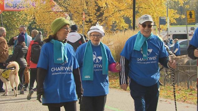 Trois personnes âgées vêtues d'un chandail Chartwell marchent en souriant lors de la marche Pierre Lavoie.