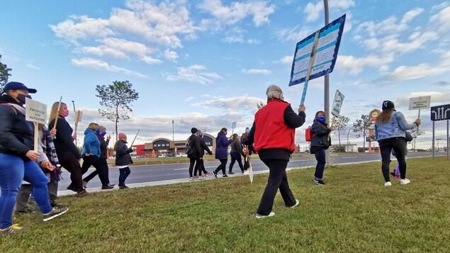 Plusieurs personnes marchent sur le trottoir du boulevard Laure à Sept-Îles.