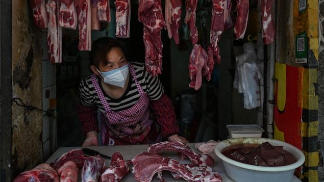 Un boucher affublé d'un masque attend des clients dans un kiosque extérieur.