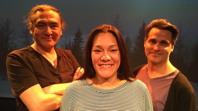 Marco Collin, Kathia Rock et Philippe Ducros, acteurs de la pièce de théâtre « La cartomancie du territoire », sourient et un paysage de forêt est projeté derrière eux.