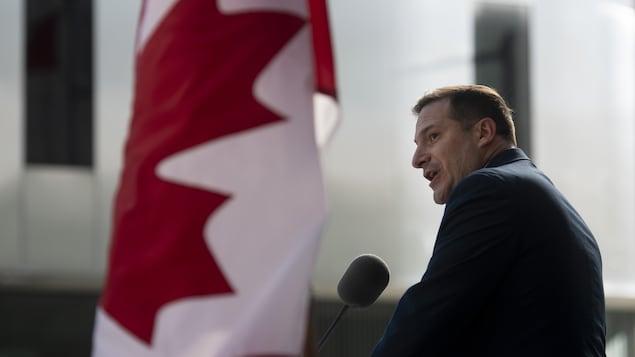 Un homme parle au micro à côté d'un drapeau canadien.