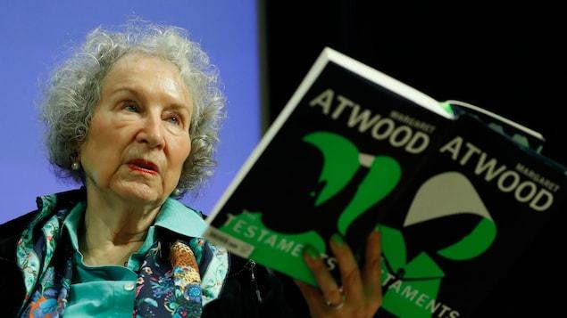 L'écrivaine tient son livre dans une main.
