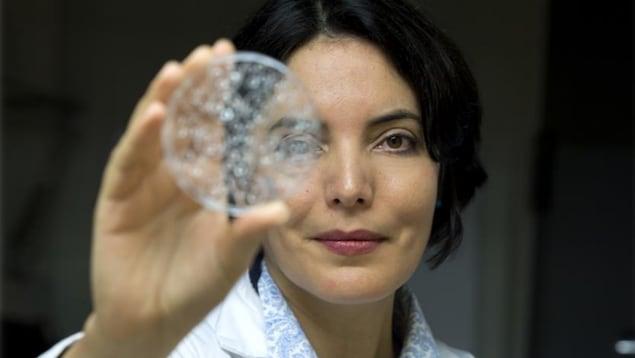 Une photo de Margaret Magdesian tenant une éprouvette circulaire devant son visage.