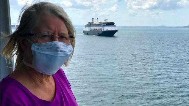 Margaret Tilley porte un masque sur le quai d'un bateau de croisière.