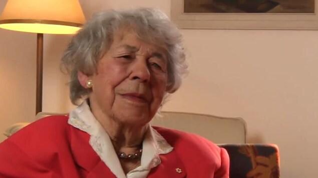 L'autrice est assise dans un salon.