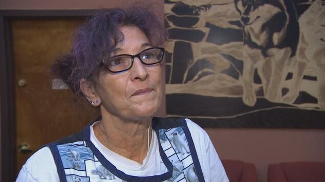 Une dame d'un certain âge avec des lunettes rectangulaires noires et des cheveux aux reflets mauves relevés regarde la caméra.