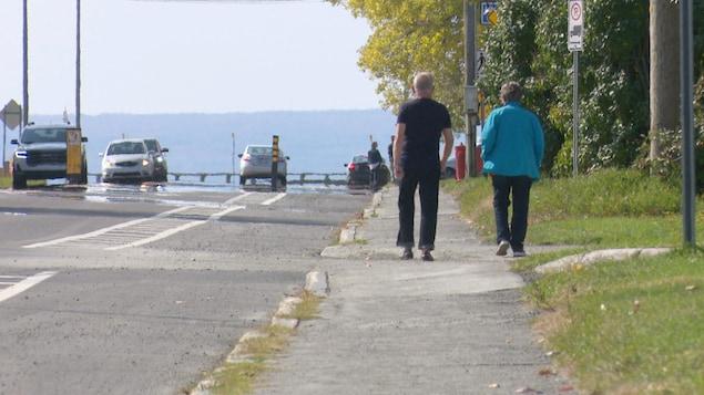Deux aînés marchent sur le trottoir à Maria.