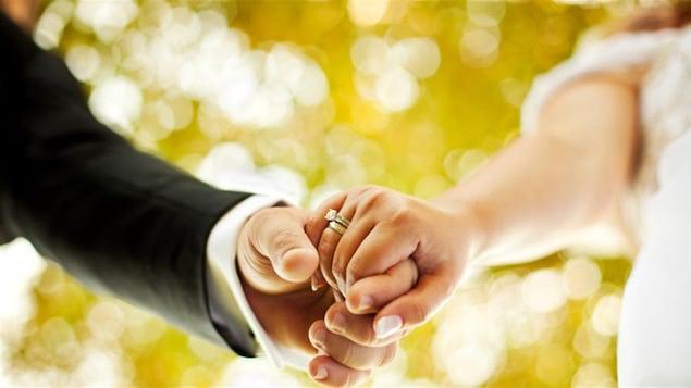 Un homme et une femme le jour de leur mariage, se tenant la main.