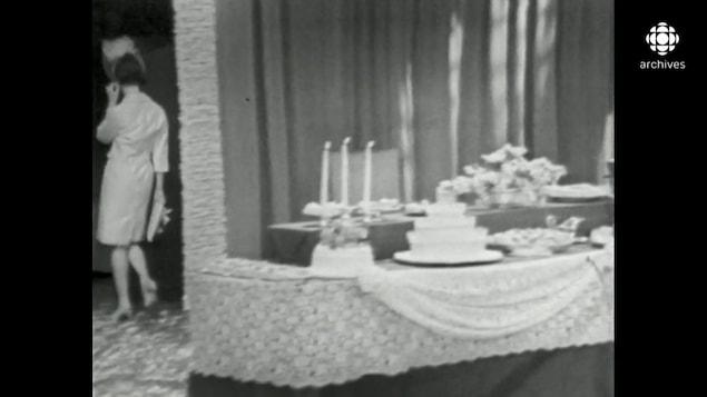 Une femme de dos, quitte une salle décorée pour un mariage avec gâteau, arrangement floral et chandelier.