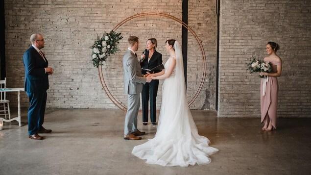 Une cérémonie de mariage : les mariés sont au centre, les témoins et la célébrante se tiennent à deux mètres de part et d'autre du couple.