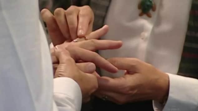 Deux femmes s'échangent des anneaux lors d'une cérémonie de mariage à Toronto.