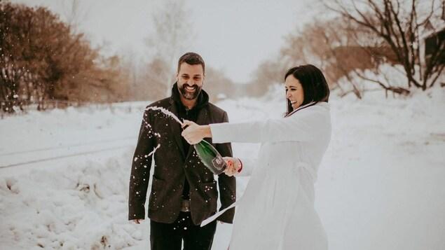 Un couple ouvre une bouteille de champagne dans la neige.