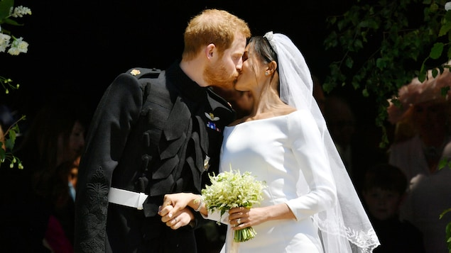Le couple s'embrasse; la mariée tient un bouquet.