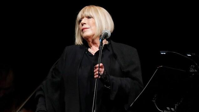 Marianne Faithfull, toute vêtue de noir, est sur scène.