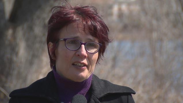 Marie Blouin en entrevue devant une rivière bordée d'arbres.