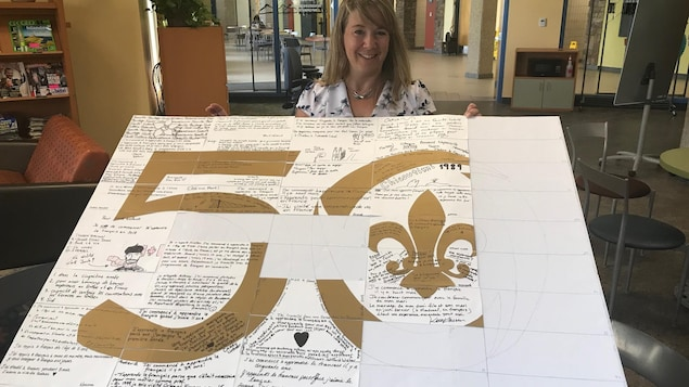 La coordonnatrice du programme d'immersion en français Marie-Eve Bussières présente une affiche du 50e anniversaire de la Cité décorée par les étudiants.